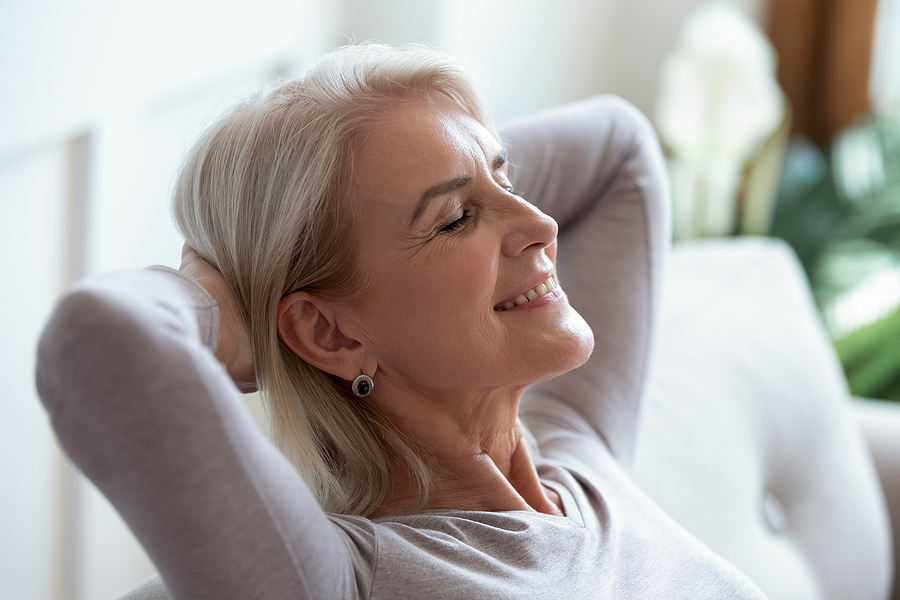 Smiling older woman relaxing with hands behind head